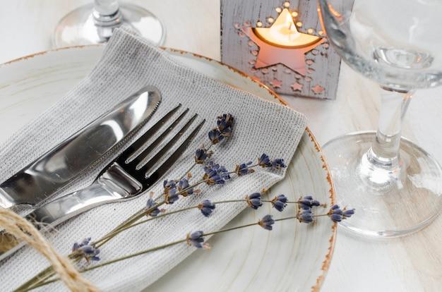 キャンドルとラベンダーのお祝いテーブルセッティング。