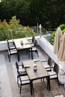 緑豊かな公園を見下ろすサマーカフェのテラスにある、色あせたテーブルと椅子。