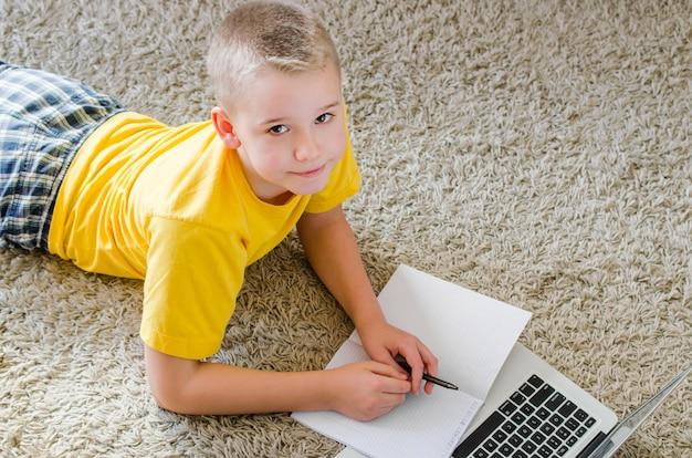 ノートパソコンを自宅で勉強している少年