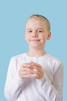 子供は彼の手で水のガラスを保持しています