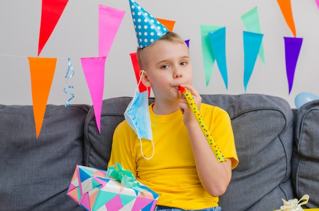 幸せな少年は彼のフェイスマスクを脱いでお祝いパイプで吹いて