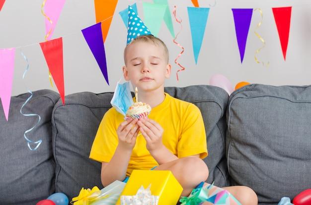 幸せな少年は彼のフェイスマスクを脱いで、休日のカップケーキを持って願い事をします