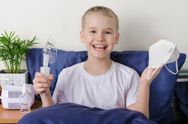 Счастливый восстановленный мальчик держит медицинскую защитную маску и маску небулайзера.