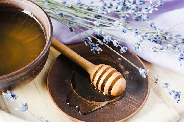 木製のテーブルの上の有機蜂蜜とラベンダーの花。