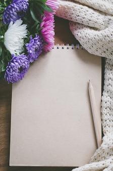 秋の花と空白の茶色のノートブック。