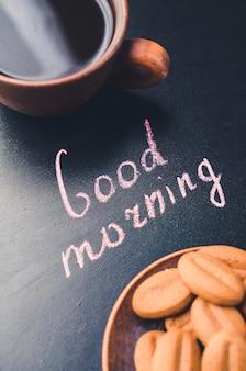 Чашка кофе и печенье на темном фоне. надпись доброе утро.