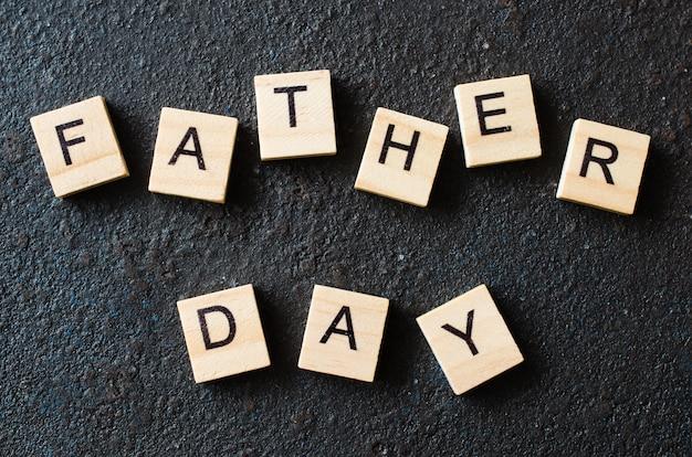 父の日の概念。暗い背景に木の手紙。
