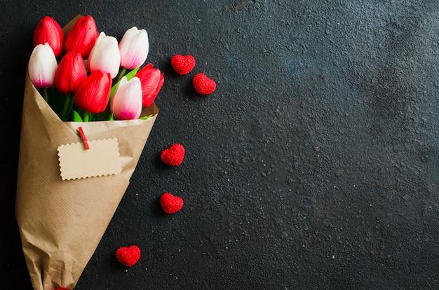 チューリップと暗い背景上のギフトボックスの花束。