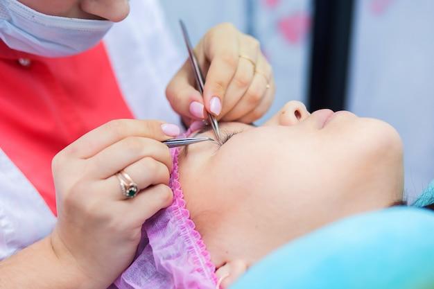 まつげエクステの達人はクライアントと美容院で働きます。少女はまつげを増やす