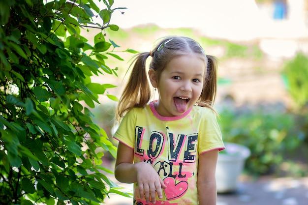 Девушка стоит возле зеленого куста и высунула язык