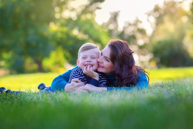 Молодая мама с сыном лежат на траве в парке и обнимаются
