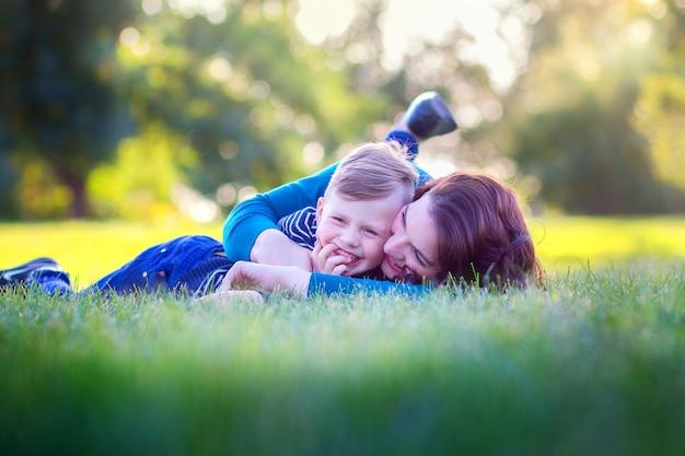 Молодая мама с сыном лежат на траве в парке и радостно обнимаются