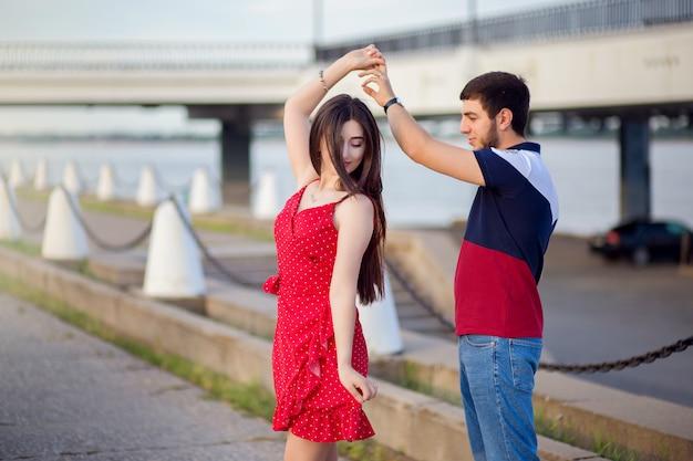 街の夏の堤防で白人の国籍の女の子のダンスを持つ男