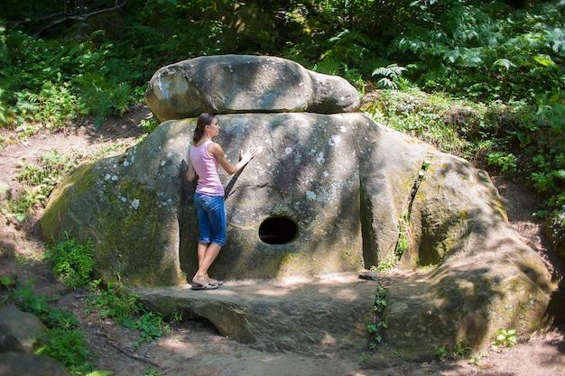 ピンクのジャージの女の子は、クラスノダール準州の古代の埋葬構造で願い事をします