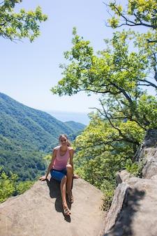 美しい自然と海を背景に高山の崖の上に座っている女の子の観光客