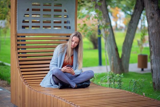 Девушка с длинными волосами и в сером свитере сидит на скамейке в парке и смотрит на смартфон