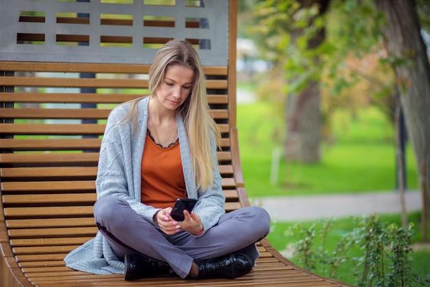 Девушка с длинными волосами и в сером пиджаке сидит на скамейке в парке и играет на смартфоне