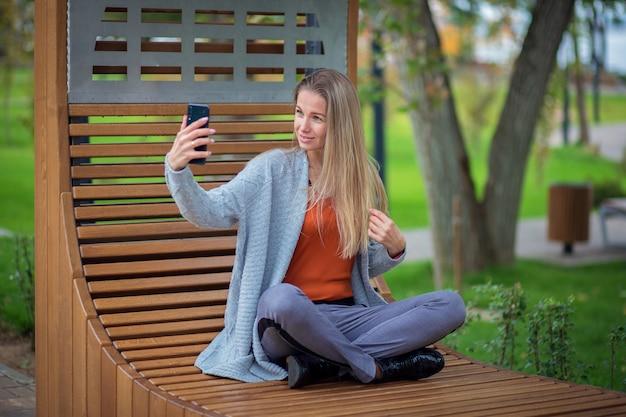Девушка с длинными волосами и в сером пиджаке сидит на скамейке в парке и делает селфи на смартфоне