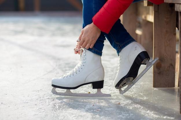Девушка в красной куртке завязывает шнурки на фигурных белых коньках на катке