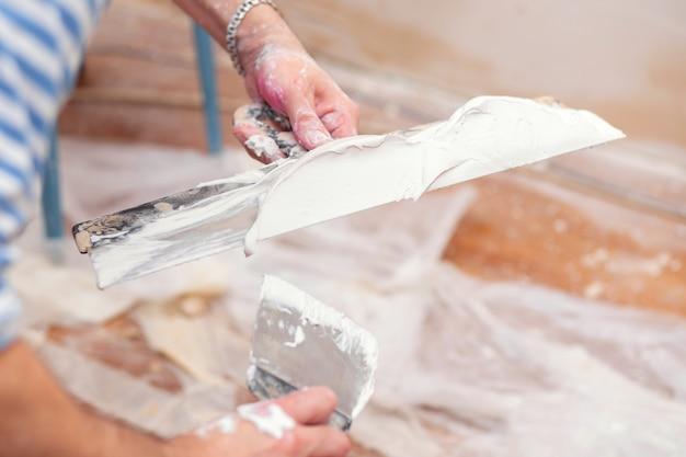 Рабочий кладет шпатель на шпатель для оштукатуривания внутренних стен в гостиной