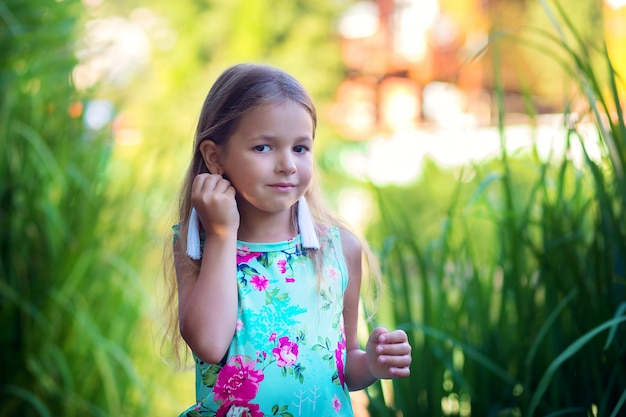 背の高い草で自然にポーズをとって長い白いイヤリングを持つ少女。ピアスを着た子供の耳のピアス