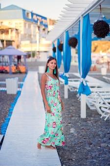 長いサンドレスで美しい少女は、観光地で海沿いの小石のビーチで木道に沿って歩く