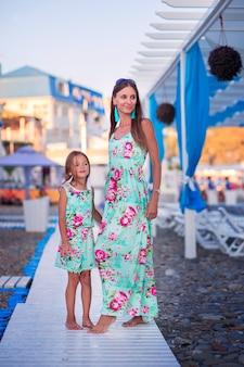 ママと娘は同じドレスを着て、観光地の海沿いの小石のビーチで木製の道を歩きます