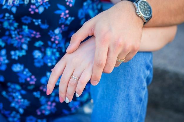 ハグカップルのクローズアップの手。男の手は女の手と戦う