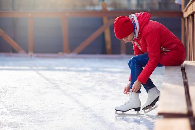 Девушка в красной куртке сидит на скамейке на открытом катке и шнурует фигурные коньки