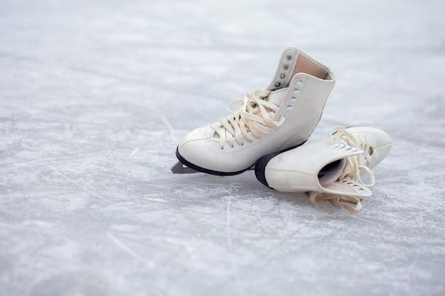 一対のホワイトフィギュアスケートは、オープンアイススケートリンクにあります。
