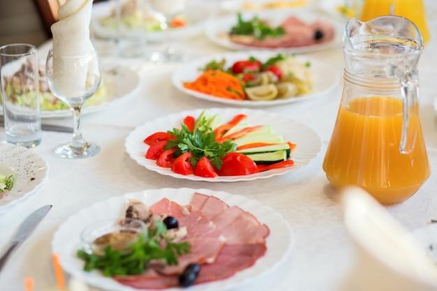 Нарезанные овощи и мясное ассорти на тарелке подают на столик в ресторане для банкета