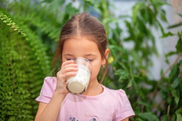 女の子は自宅で透明なガラスからケフィアを飲みます。赤ちゃんのための適切な栄養