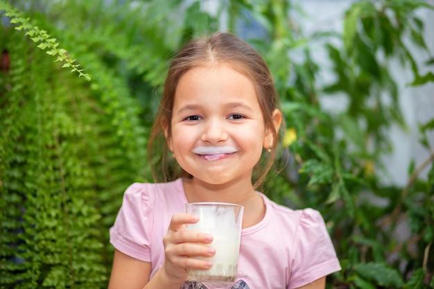 少女はグラスからケフィアまたは牛乳を飲んで微笑んだ。ケフィアの口ひげ