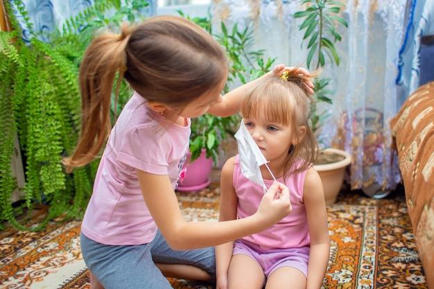 女子高生は彼女の妹に医療マスクを置く