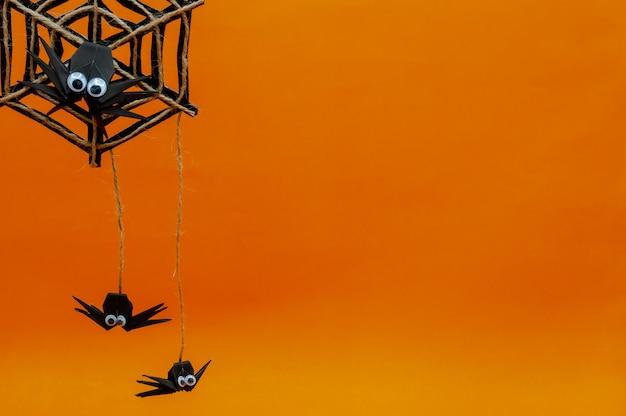 オレンジに分離されたクモの巣に掛かっているクモの折り紙ハロウィーンの背景。