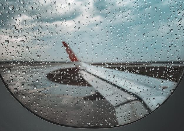 モンスーンの季節に離陸する前に飛行機の窓に雨が降る。
