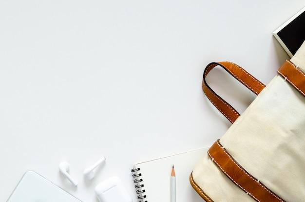 学校は、学生の本、ノート、鉛筆、学校のコンセプトに戻るためのワイヤレスイヤホンと現代のスマートフォンが付いているバッグを運ぶ。トップビュー、フラットレイアウトの背景