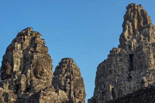 空から青い色の背景を持つカンボジアのシェムリアップの古代バイヨン寺院の顔。