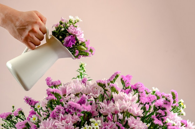 色とりどりの花の花束に水をまく白い鍋を持っている手。