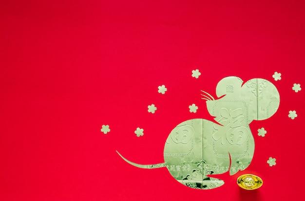 Китайское украшение фестиваля нового года на красной предпосылке которая отрезала в форме крысы положила дальше пакеты золота денег.