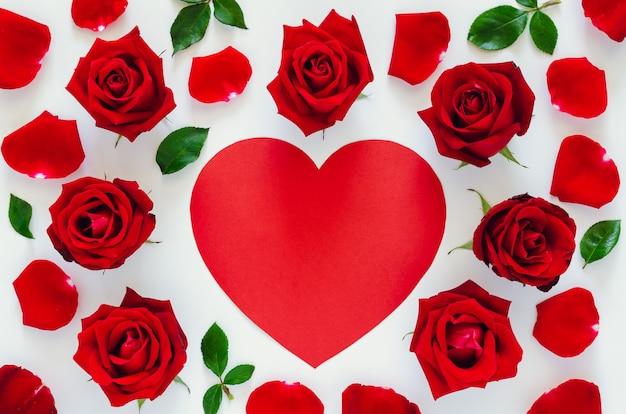 サンバレンタインの日に赤いハート形のスペースで白い背景にその花びらと葉の赤いバラを置く