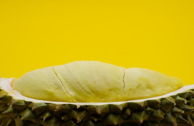 テキスト用のスペースと黄色の背景に分離されたタイからの果物の王様である新鮮なカットドリアン。