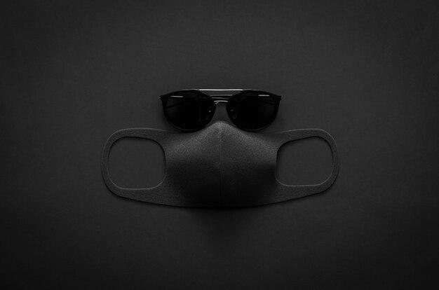 サングラスとフェイスマスクは、シンプルなフラットレイアウトブラックコンセプトの暗い背景にウイルスを保護します。