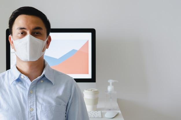 コーヒーカップと作業テーブルのアルコールゲルで事務室のウイルスを保護するためにマスクを身に着けているアジアの男性将校。