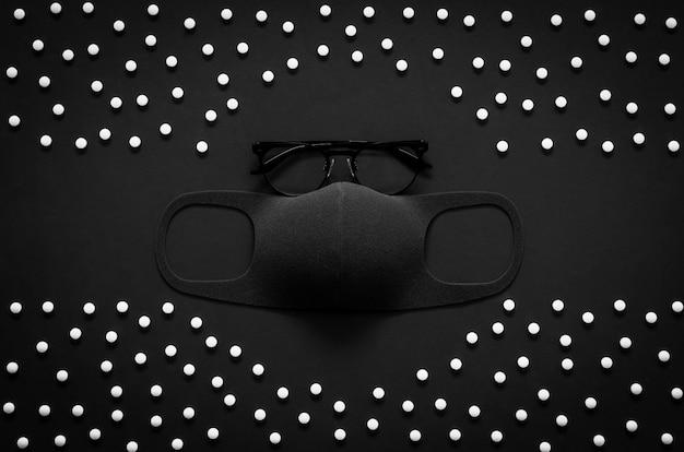 平らな黒いコンセプトの暗い背景に白い錠剤でウイルスを保護するための眼鏡とフェイスマスク。