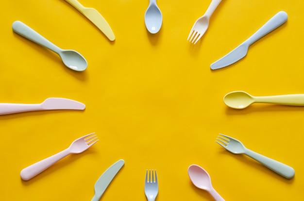 カラフルなフォーク、スプーン、ナイフの真ん中にテキスト用の空のスペースで黄色の背景に。