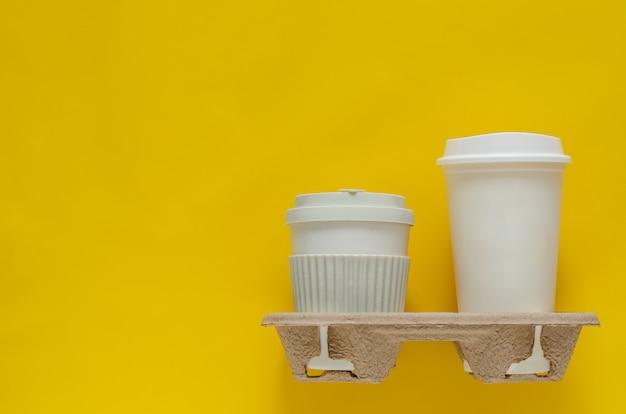 再利用紙トレイにコーヒーのリサイクルカップは、世界環境の概念のために置きました。