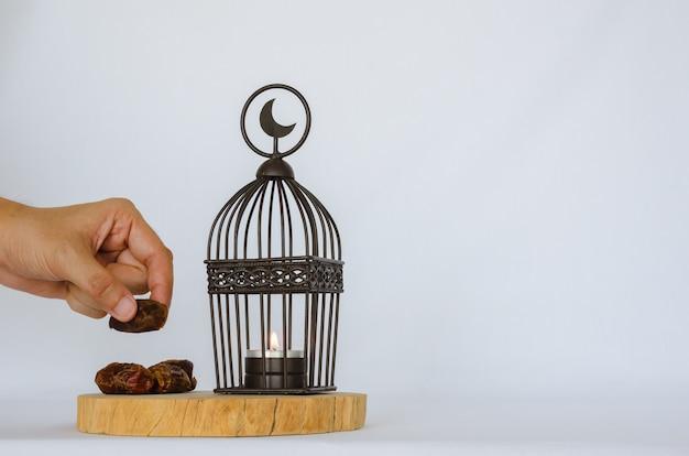 ラマダンカリームの聖なる月のイスラム教徒の饗宴のための白い背景の上の木製トレイに置く上に月のシンボルがあるランタンと日付のヤシの果実を持っている手。