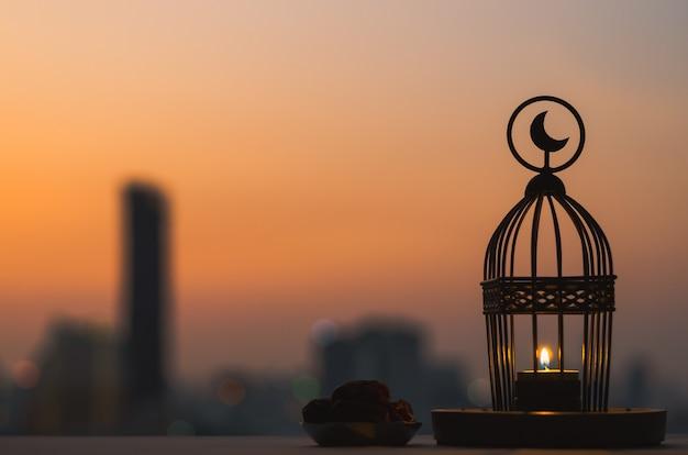 ラマダンカリームの聖なる月のイスラム教の饗宴のための夕暮れの空と街の背景を持つ日付と果物の上部と小さなプレートに月のシンボルがあるランタン。