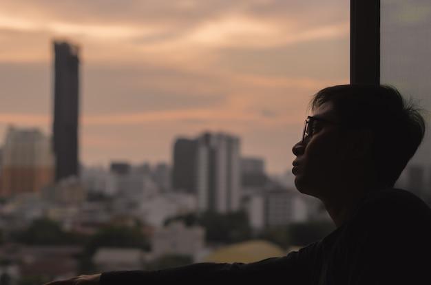 部屋から街の景色を眺めている男性